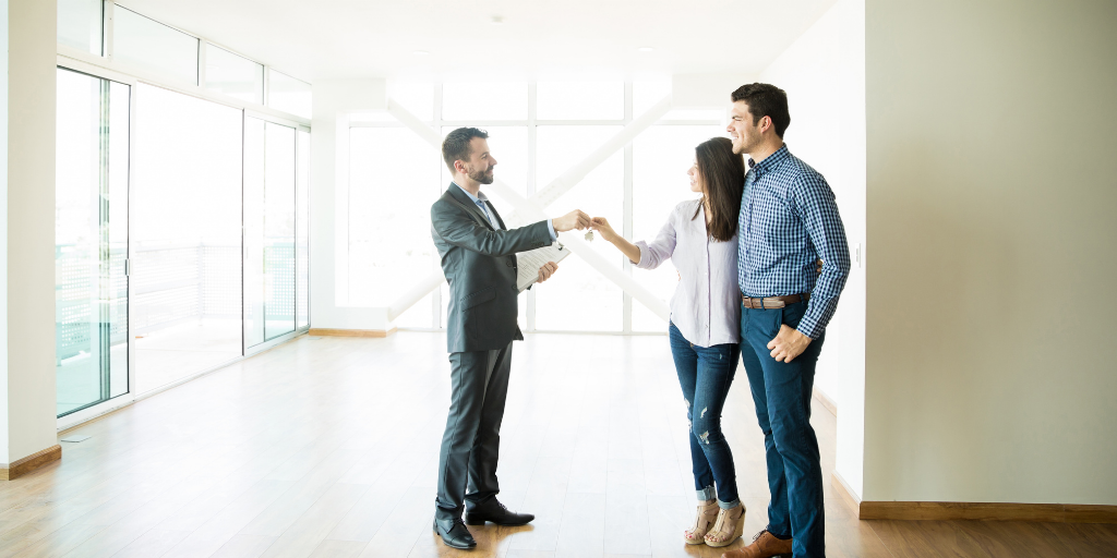 Couple getting keys to a new house from real estate agent